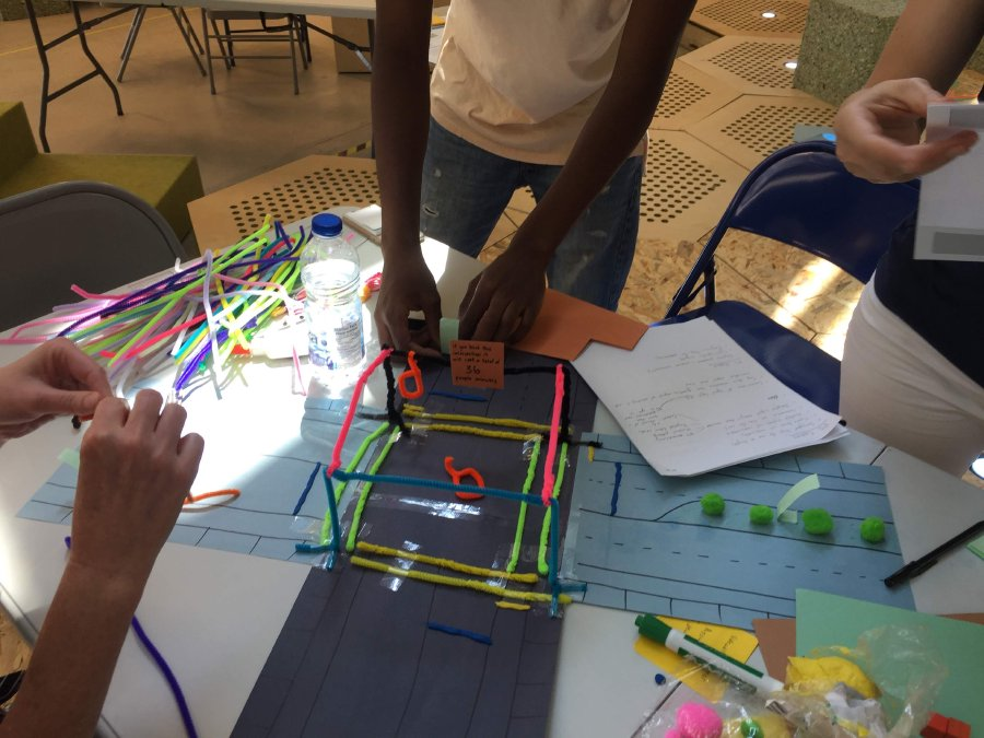 Participants from group Harmony building a prototype of an optimized intersection for cyclists and pedestrians using different colored cleaning pipes and construction paper