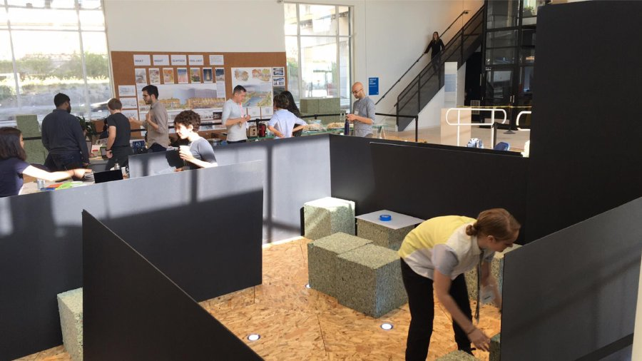 One participant arranging foam cubes inside the Tranquil Refuge model to build the interior seating area